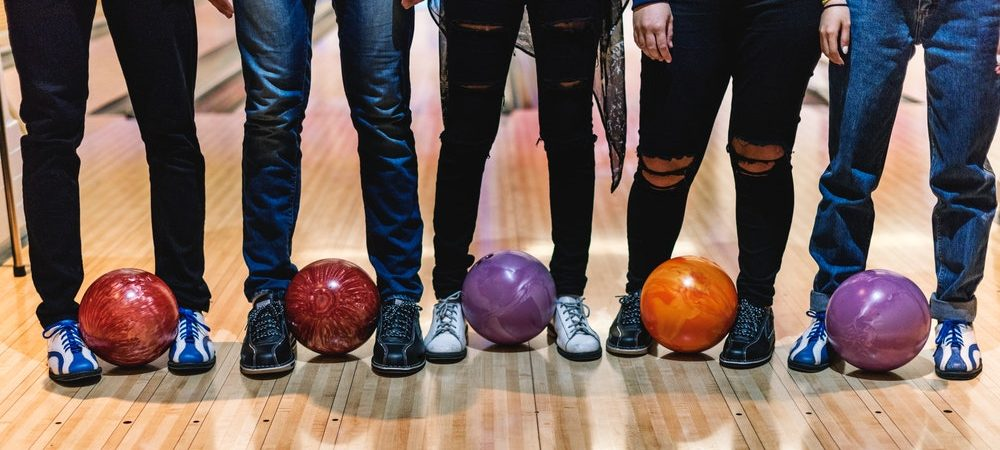 Five people are shown standing from the waist down with bowling balls between their feet.