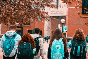 Students shown from behind wearing backpacks on a college campus.