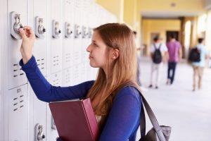 A high school girl opening her locker.