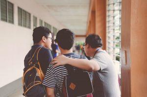 Three boys facing away wearing backpacks.