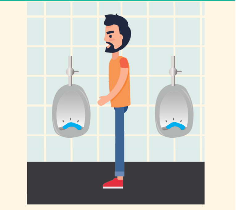 A man stands in the center of the bathroom, being careful not to touch the urinal with his hands.