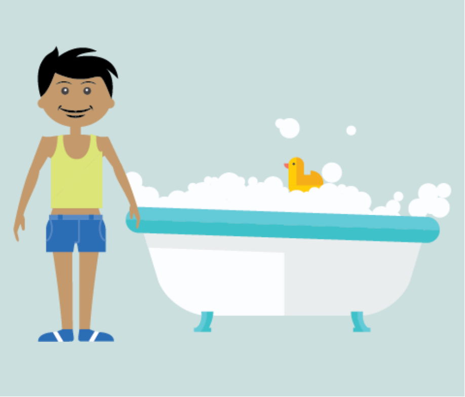 Young boy stands next to bathtub.