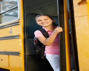 A young girl with a backpack getting on the school bus