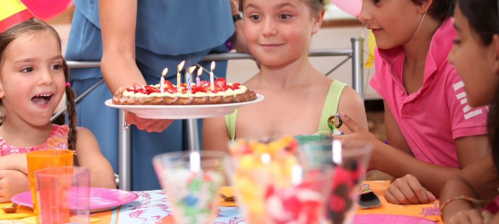An adult puts a birthday cake on the table. There are kids wearing party hats