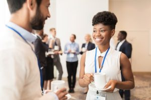 A woman is smiling, holding a cup of coffee, and is talking to a man. They are both at a conference