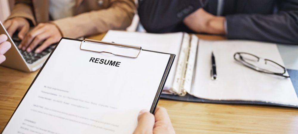 An individual holding a resume before two other business individuals.