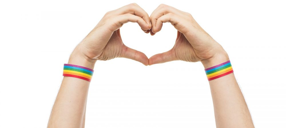 Two hands making a heart. They have rainbow wristbands