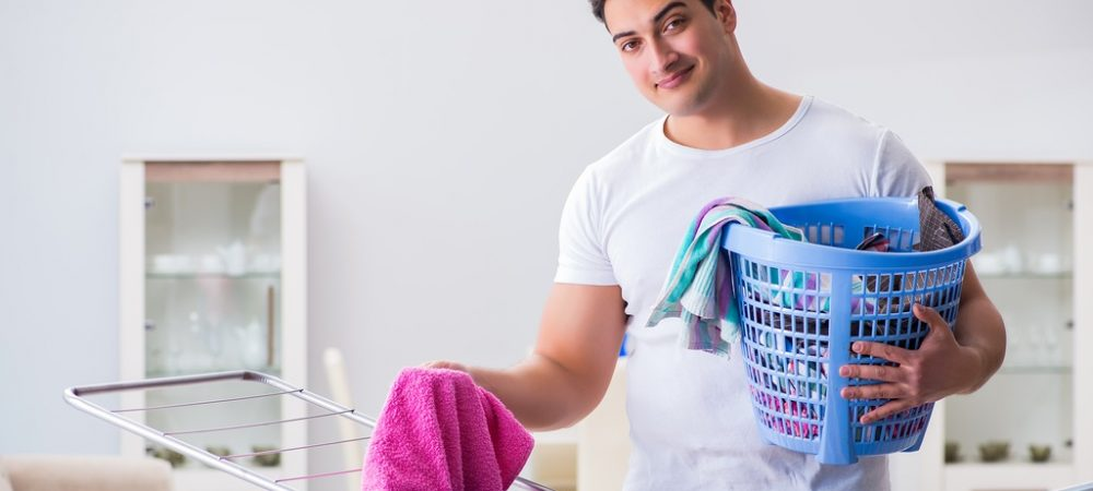 A man holding a laundry basket and hanging up laundry