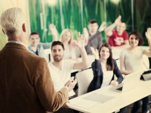 A professor teaching his class. The students are raising their hands.