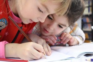 Two young girls look at a notebook and draw with a pencil.
