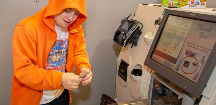 A young man wearing a hoodie is seen collecting change from a grocery store self-check machine.