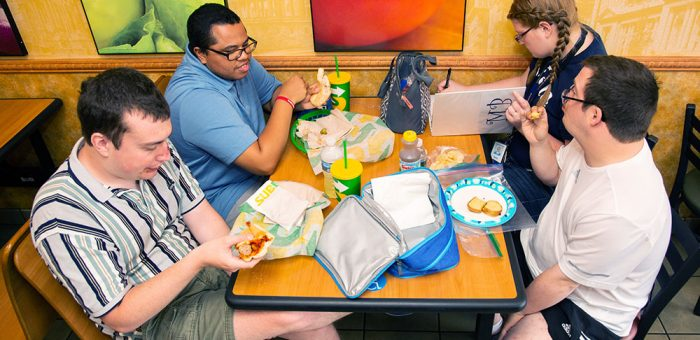 Four young adults are seen sitting in a sandwich shop, eating a meal together and talking.