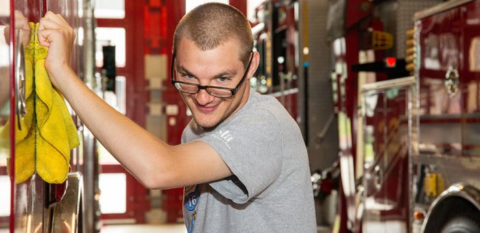 A young man is seen polishing a fire truck in a fire station. He is looking at the camera happily.