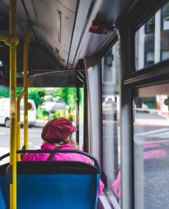 A woman is shown from behind sitting in a bus looking out the window.